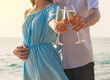 Couple with champagne in glasses on the beach. Love and wedding in tropical countries concept.