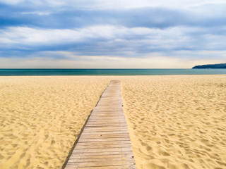 FototapetaWooden boardwalk to the sea on a sandy beach