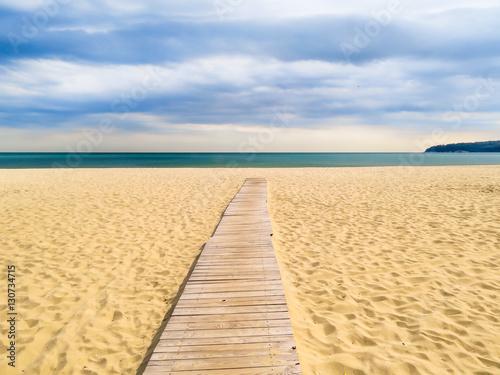 Wooden boardwalk to the sea on a sandy beach