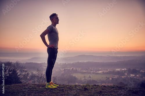 Photo Ragazzo fa stretching al parco in cima alla collina con vista sulla città