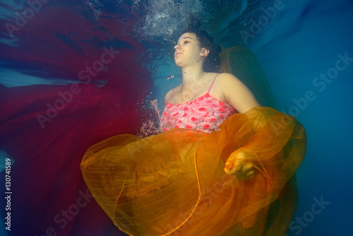 Wall Murals Mermaid Pregnant girl swims underwater and plays with red and yellow cloth on light blue background. Portrait. The view from under the water. Horizontal orientation