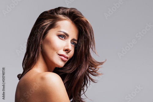 Fotografering Studio portrait of a beautiful young woman with long brunette hair