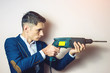 man businessman holds in hand a power drill as weapon