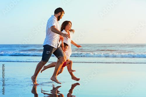 Plakat Szczęśliwa rodzina - ojciec, matka, dziecko syn trzymać się za ręce, biegać wraz z plamami przez basen wody wzdłuż morza zachód surfować na plaży z czarnym piaskiem. Podróże, aktywny tryb życia, rodzice z dzieckiem na wakacjach.