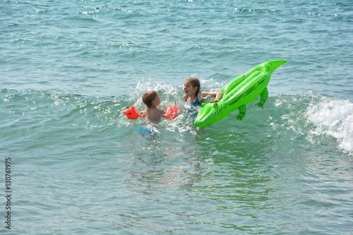 Fotografie, Obraz  Zwei Kinder schwimmen auf einer Krokodil - Luftmatratze in den Meeres Wellen