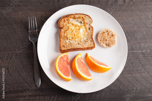Fotografie, Obraz  Toad in a hole egg breakfast with Cara Cara oranges top view