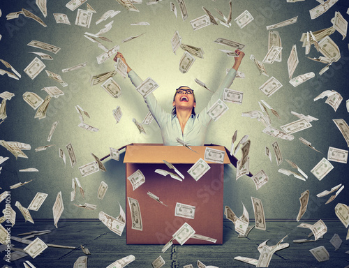 Successful woman coming out from a box under money rain Fototapeta