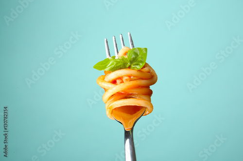 Fork with tasty pasta and basil on color background, close up view Fototapeta