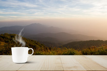 Hot Coffee Cup With Steam On Vintage Wooden Table Top On Blurred Meadow And Foggy Mountain Background During Sunrise
