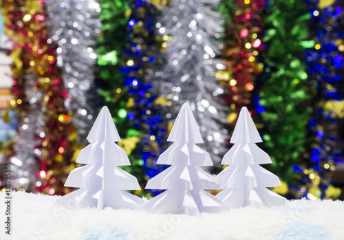 white origami christmas tree on colorful blurred background for create xmas and happy new