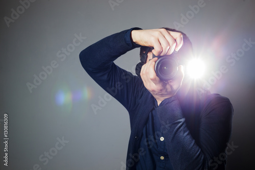 Obraz Photographer takes a picture in the studio using a flash - fototapety do salonu