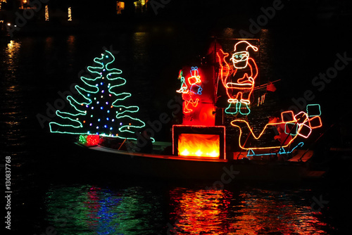 Photo There goes the Merry Christmas float, bedecked in colorful lights, to share the joy of the holiday with Santa on his boat