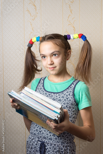 Photo  11 year old girl with funny tails is with a pile of books