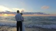 Wedding. Newly married couple on the beach at amazing sunset , Romantic nature environment. Bride and groom. Slow motion footage.