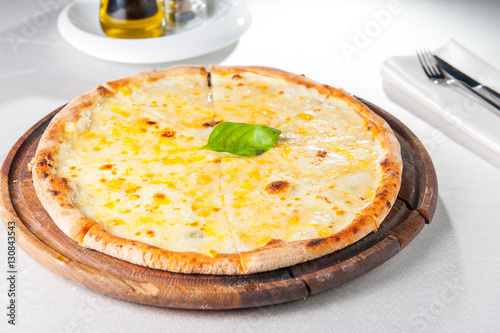 Four Cheese Pizza Quattro Fromaggi With Basil Leaf On A Rustic Wooden Board  On The Served