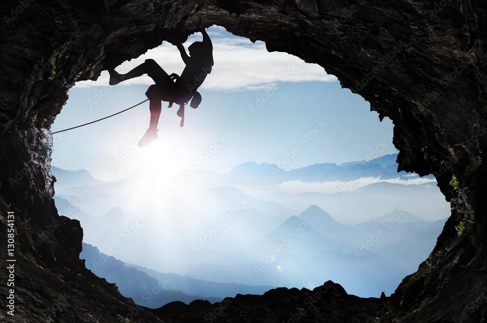 Fototapeta Bergsteiger im Hochgebirge an einem Höhlenausgang