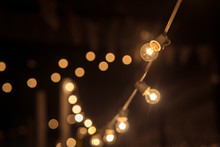 Garland Of Lights. Vintage Style. Background Of Light Bulbs In A Field In The Rest Blurring. Party And A Modern Café Design Concept. Modern Decoration Garland Of Electric Bulbs Edison .