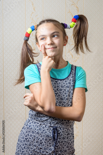 Fotografie, Tablou 11 year old girl with pigtails like Pippi Longstocking is thoughtfully, pressing a finger to her cheek
