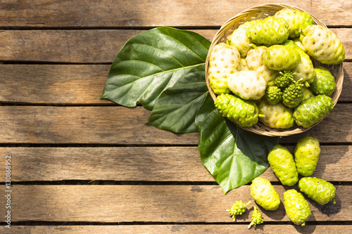 Noni fruit and noni in the basket on wooden table.Top view Canvas Print