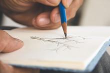Man Writing A Tree On Sketchbo...