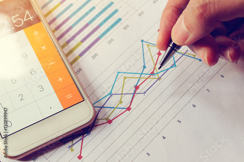 Fotografía Businessman holding pen and think with cost with calculator in s
