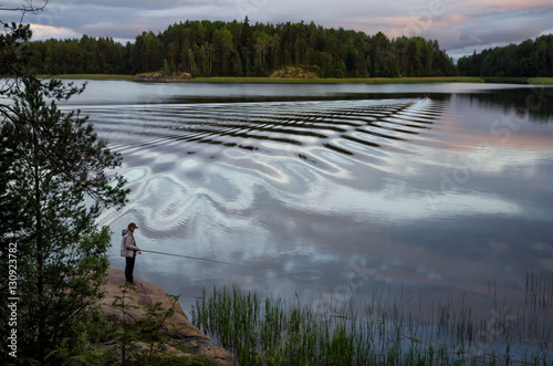 Photo  Fisher-woman standing on a rock with a fishing rod and fishing