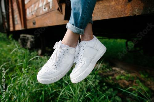 Fotografia Female sneakers. White female shoes on feet. Sneakers closeup.