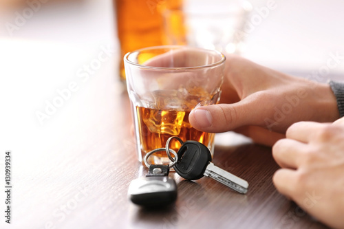 Fotografering  Man sitting in bar with alcoholic beverage and car key, closeup