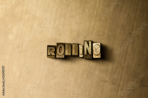 Photo  ROLLING - close-up of grungy vintage typeset word on metal backdrop
