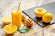 freshly squeezed orange juice in glass bottle on wooden background