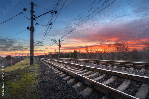 Photo sur Toile Gris traffic Railway station against beautiful sky at sunset. Industrial landscape with railroad, colorful blue sky with red clouds. Railway junction. Heavy industry. Cargo shipping. Railway sleepers. Travel