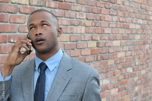 Photo  Portrait of bored businessman talking on cellphone against brick wall background