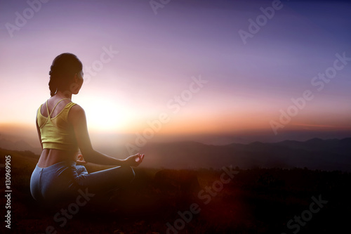 Young girl doing yoga at the mountain in the twilight.
