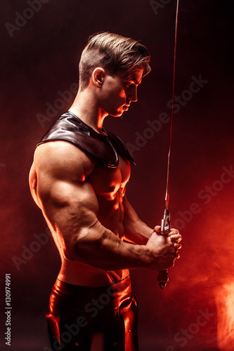 Fotografering  Portrait of sexy muscular concentrated man holding sword.