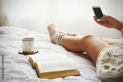 Fototapeta Soft photo of woman on the bed with old book, a cup of coffee and smart phone obraz na płótnie