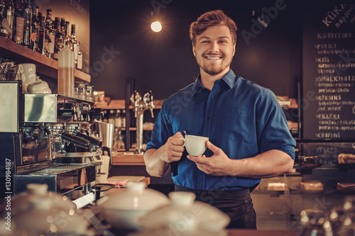 Fotografie, Obraz  Handsome barista tasting a new type of coffee in his coffee shop