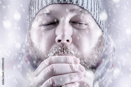 Vászonkép Freezing cold man  snow storm storm white out trying to keep warm by blowing into his hands