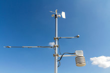 Anemometer, Temperature And Humidity Meteorological Instrument On The Pole Against The Clear Blue Sky.