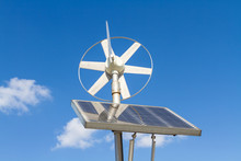 Wind And Solar Power System Against The Clear Blue Sky.