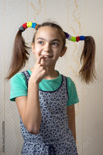 Fotografie, Tablou 11 year old girl with pigtails like Pippi Longstocking with a mischievous look on her face and her finger to her mouth thoughtfully looking up