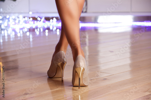 Fotografia Woman wearing gold elegant high-heeled shoes.