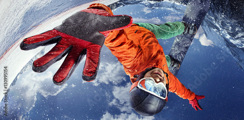 Sport background. Winter sport. Snowboarder jumping through air with deep blue sky in background.