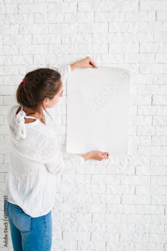 Fotografía  Young woman looking at empty sheet of paper, mockup