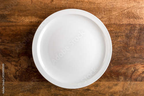 Empty white plate on wooden table, top view