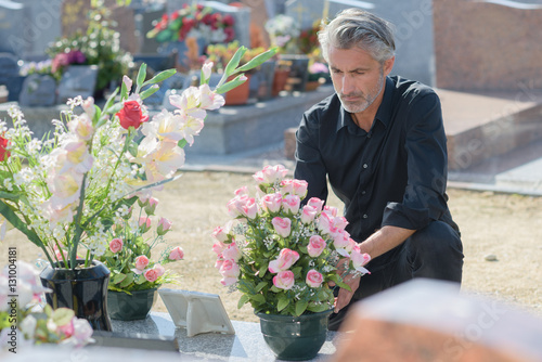 Recess Fitting Cemetery Man putting flowers on tomb
