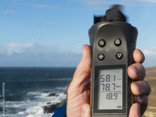 Hand holding up a anemometer and measuring the wind speed in kil