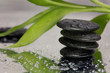 Spa concept. Volcanic rocks and bamboo on reflective background with raindrops. Relaxation, body care treatment, wellness