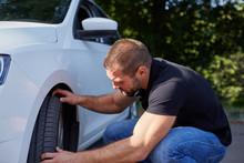 Man Examining Tires At His New Car