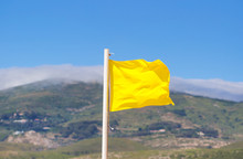 Yellow Flag Waving On The Beach In The Breeze Against A Blurred Blue Sky.