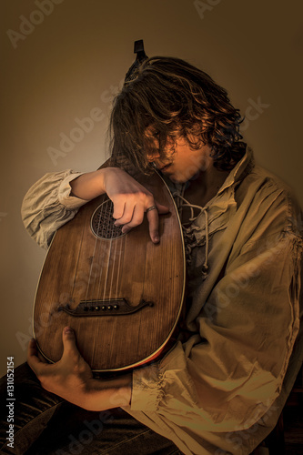 Young man with long blond hair sitting in dark environment and hold in His Hands and hug an Old Oud, Guitar Lute Canvas Print